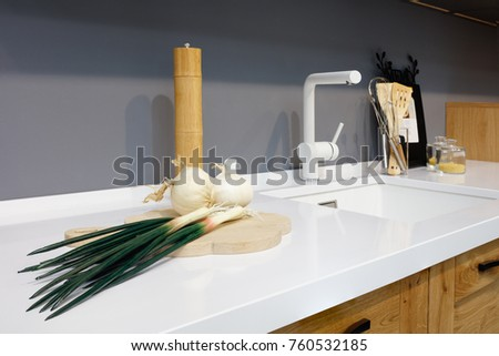 Kitchen interior, glass jars with grains in modern kitchen with white mixer, green onion, garlic, spices, wooden chopping board; white table top, interior of modern kitchen Stock fotó ©