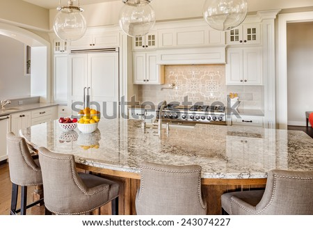 Kitchen Interior in New Luxury Home with Island, Sink, Cabinets, and Hardwood Floors