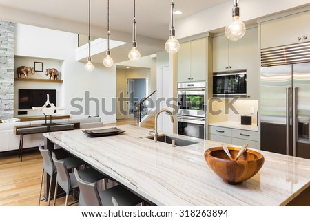 Kitchen Interior in New Luxury Home with Island, Sink, Cabinets, and Hardwood Floors and View of Living Room