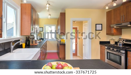Kitchen interior in wood with counter top beige walls, granite counter tops, stainless steel appliances and rectangle wash basin.