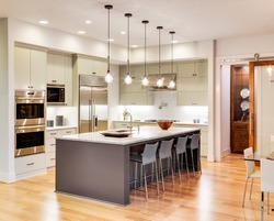 Kitchen Interior with Island, Sink, Cabinets, and Hardwood Floors in New Luxury Home