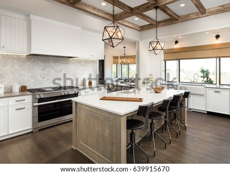 Photo of Kitchen Interior with Island, Sink, Cabinets, and Hardwood Floors in New Luxury Home. Features Elegant Pendant Light Fixtures, and Farmhouse Sink next to Window