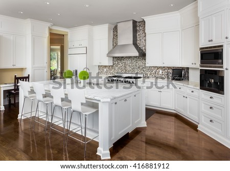 Kitchen Interior with Island, Sink, Cabinets, Oven, Range, and Hardwood Floors in New Luxury Home #416881912