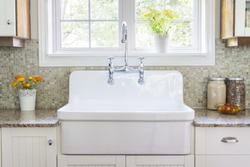 Kitchen interior with large rustic white porcelain sink and granite stone countertop under sunny window