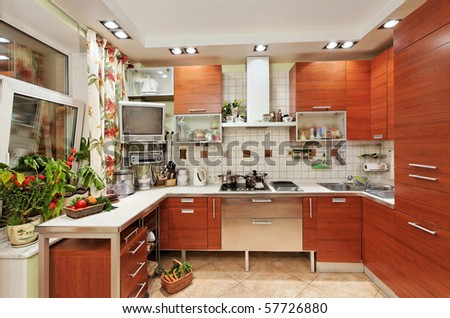 Kitchen interior with wooden furniture and many utensils in warm tones on wide angle view