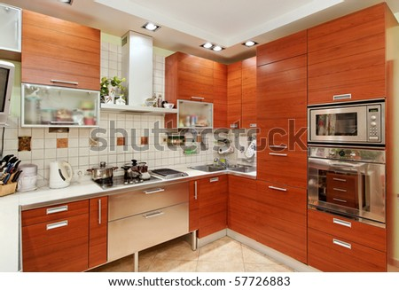 Kitchen interior with wooden furniture and many utensils in warm tones on wide angle view - stock photo