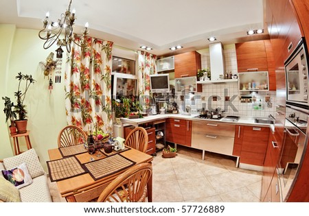 Kitchen interior with wooden furniture, table and many utensils in warm tones on wide angle view