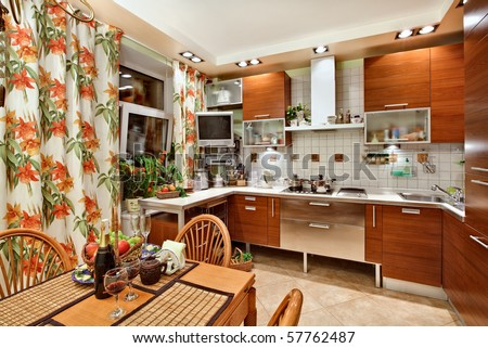 Kitchen interior with wooden furniture, table and many utensils in warm tones on wide angle view - stock photo