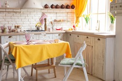 kitchen interior with yellow curtains and yellow tablecloth on the table