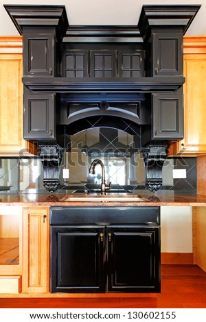 Kitchen island and stove custom wood cabinets. New luxury home interior.