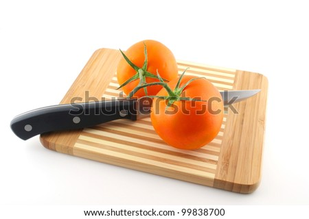 Kitchen-knife and red tomatoes on the preparation board