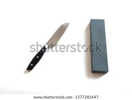 Kitchen knife and sharpening stone on a white background- image