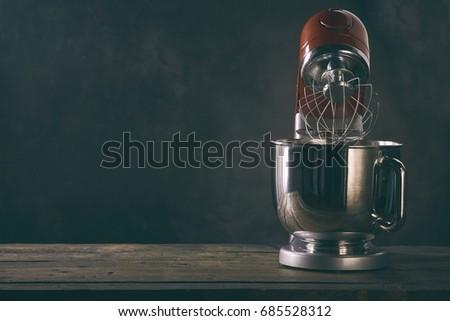 Kitchen mixer standing on wooden countertop against dark background
