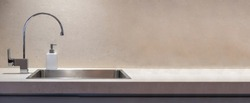 Kitchen modern interior detail. Kitchen sink and water tap front view, Stone beige color countertop banner, copy space