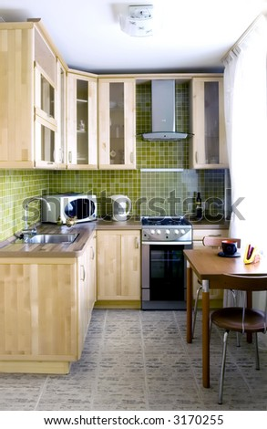 Kitchen - natural wood cabinets with glass and stone tiles