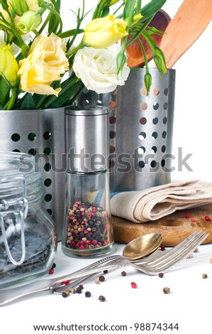 Kitchen objects, cookware, tableware, flowers and spices on a white background.