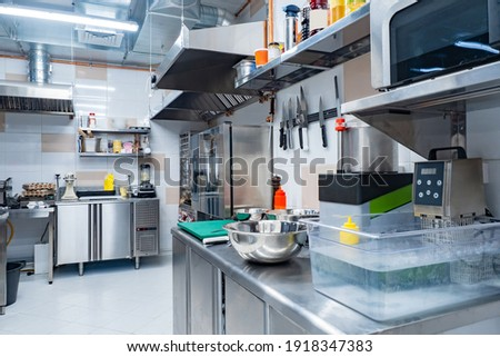 Kitchen of a working restaurant without people. No one is inside cafe kitchen. Concept - work in restaurant kitchen. Work as cook in a cafe. Career in horeca industry. Chromed equipment in cook room