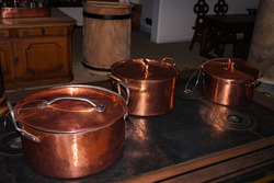 Kitchen of the old castle. Copper pans, baking molds and other kitchen utensils