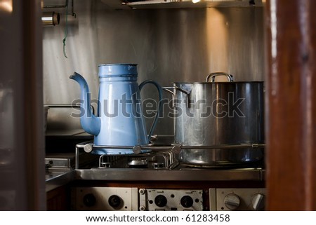 "Kitchen on board a very old wooden galley with an old ""madam blue"" coffea pot on the stove"