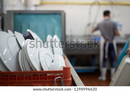 Kitchen porter cleaning white plates in sink in professional kitchen. dish washer Сток-фото ©