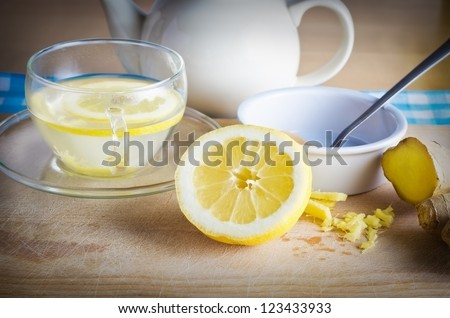 Kitchen preparation scene containing ingredients for a honey, lemon and ginger drink - a herbal home remedy for colds.