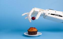 Kitchen robotization. Robot hand putting fresh cherry on top of the cupcake, blue background