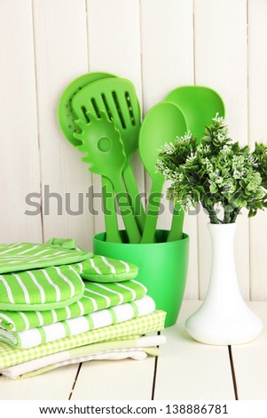 Kitchen settings: utensil, potholders, towels and else  on wooden table