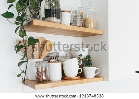 Kitchen shelves with various white ceramic and glass jars. Open shelves in the kitchen. Kitchen interior ideas. Eco friendly kitchen, zero waste home concept