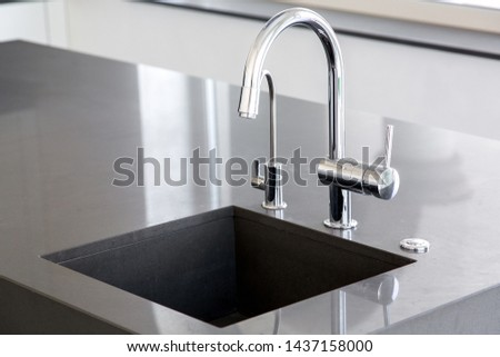 kitchen sink of dark gray stone with chrome faucet in a clean kitchen with a glossy work surface, close up faucet sink.