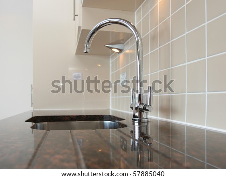 Kitchen sink with mixer tap recessed into granite work surface.