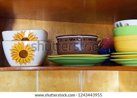 Kitchen still life: stacks of colorful dishware on shelf of the kitchen cupboard. Colorful ceramic crockery on a wooden shelf.