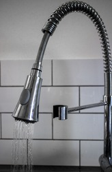 kitchen tab with flexible hose against white tiled wall with spray of water