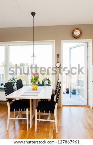 kitchen table by the window and open door to the balcony