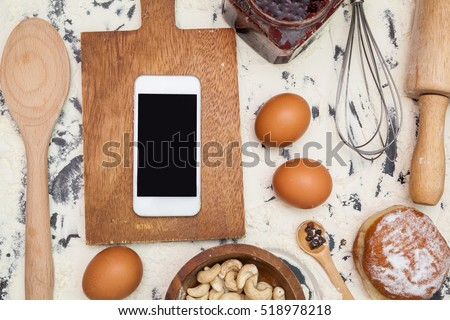 Kitchen table with ingredients, utensils and smartphone with blank screen for your app over cooking book on wooden table. Top view. Recipe and menu background