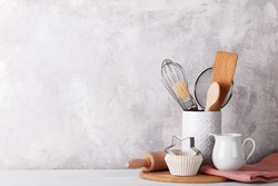 Kitchen table with white modern ceramic and wooden dishware against grey stone wall, baking utensils copy space