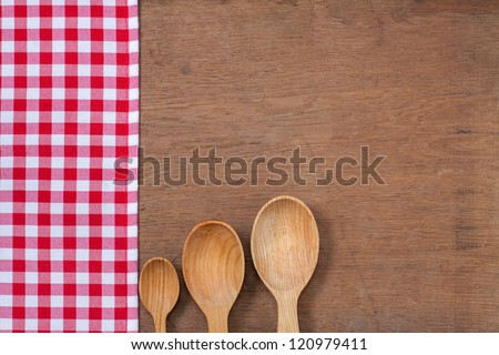 Kitchen tablecloth, wooden spoons on table background