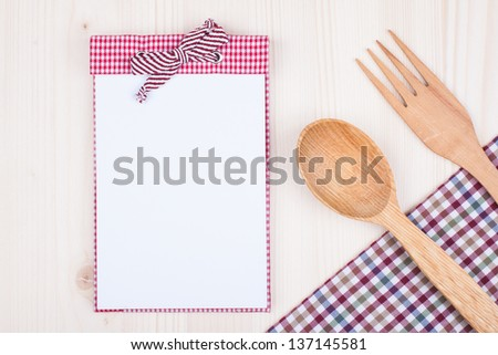 Kitchen textile, wooden spoon, fork, recipe book on wood textured background