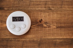 kitchen timer on a wooden table with a time set to five minutes