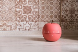 Kitchen timer shaped like a apple stands on the kitchen counter top, counting down fifteen minutes