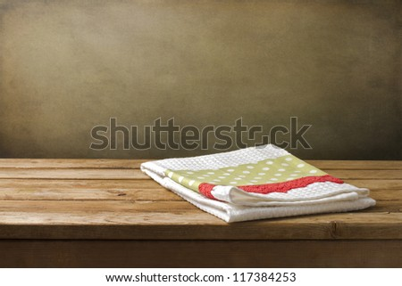 Kitchen towel on wooden table over grunge background