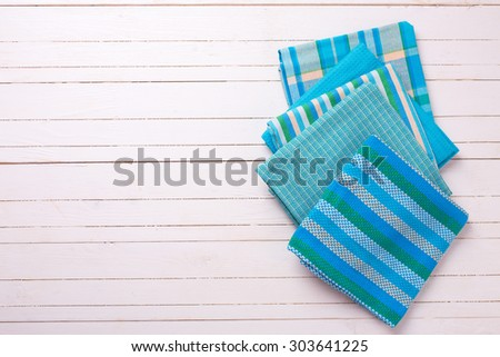 Kitchen towels in blue colors  on white wooden background. Selective focus. Place for text.