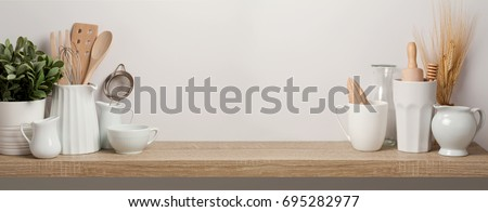 Kitchen utensils and dishware on wooden shelf