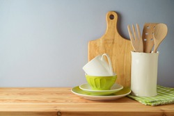 Kitchen utensils and dishware on wooden table. Kitchen interior spring background