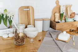 Kitchen utensils and dishware spring flowers on wooden table. Kitchen interior background white ceramic brick wall background. Eco friendly kitchen concept