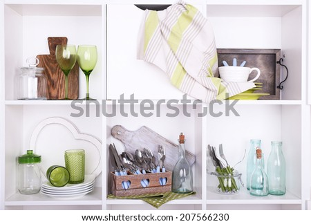 Kitchen utensils and tableware on beautiful white shelves