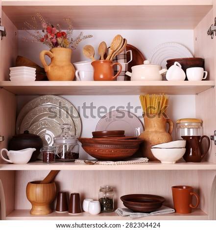 Kitchen utensils and tableware on wooden shelves