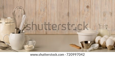 Kitchen utensils and tools for homemade baking on a light wooden background. Selective focus. #720997042