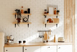 Kitchen utensils and utensils on a wooden countertop. Stylish kitchen interior in white and beige tones, spring background