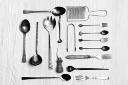Kitchen utensils background - spoons, forks, cheese knife, grater, tongs