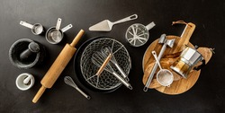Kitchen utensils (cooking tools) on black chalkboard background - horizontal banner layout. Kitchenware collection captured from above (top view, flat lay).